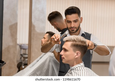 Side view of barber concentrated on shaving man's beard using sharp razor. Handsome hairstylist wearing in white t shirt, black vest, and black gloves. Client covered with striped haircut gown.