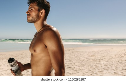 Side view of a bare chested man standing on a beach during workout holding a water bottle. Athletic man standing on beach taking a break while doing fitness workout.