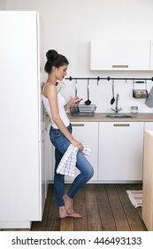 Side view of barefoot brunette with towel leaning on fridge in kitchen and chatting via phone