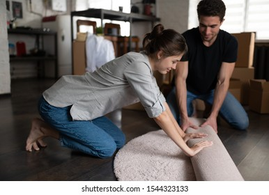 Side view of barefoot young female smiling and unrolling white carpet with boyfriend while decorating room of modern flat together