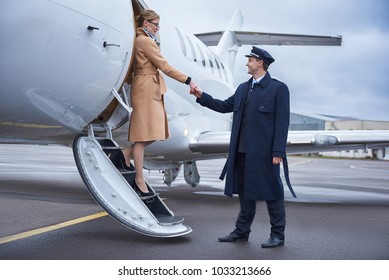 Side view beaming aviator helping cheerful lady going down from aircraft. Profession and journey concept