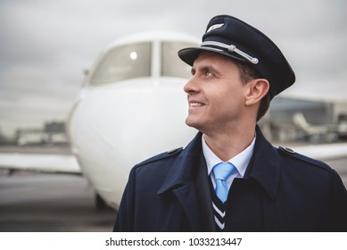 Side view beaming young aviator situating opposite aircraft on street. Labor concept