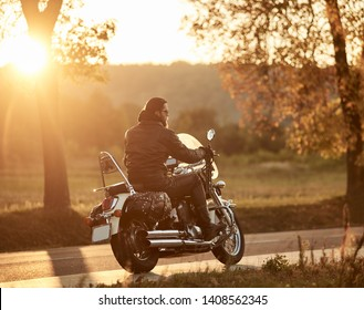 Side view of bearded biker riding modern powerful high-speed motorcycle along empty narrow country road on lit by bright setting sun, beautifull golden autumn landscape background.