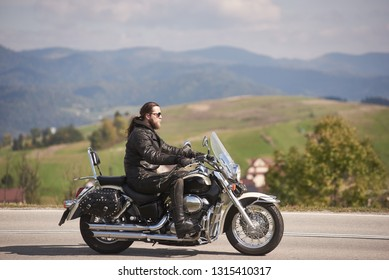 Side view of bearded long-haired motorcyclist in sunglasses and black leather clothing riding cruiser motorbike along narrow asphalt path on sunny autumn day.