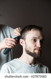 Side view of bearded man getting haircut by hairdresser at the barbershop