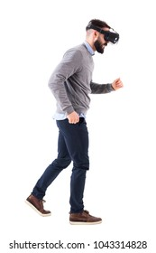 Side view of bearded man watching virtual reality glasses running and looking down. Full body isolated on white background.