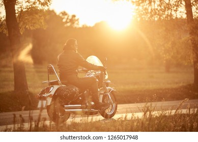 Side view of bearded motorcyclist riding modern powerful cruiser motorcycle along empty narrow country road at sunset on beautifull golden autumn landscape background.