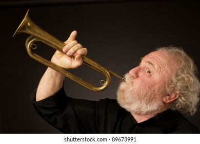 Side view of a bearded senior musician blowing a bugle, held with an expressively raised little finger. Black background, horizontal format and copy space.