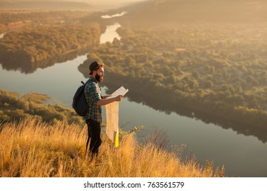 Side view of bearded tourist on hill at river standing with map.
