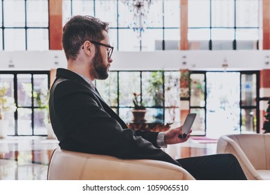 Side view of a bearded young successful man employer in a formal suit sitting in a beige armchair in the lobby of his office, waiting and using his smartphone; a glass facade behind him