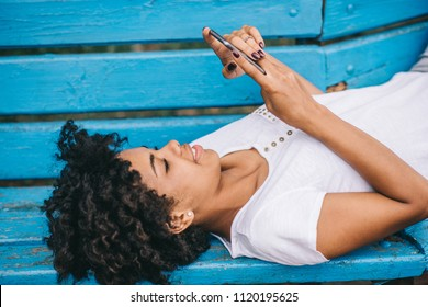 Side view of beautiful african american female student lying outdoors in the park reading news and messaging via social networks using smart phone using free wireless. People and lifesetyle concept