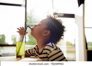 side view of beautiful african american boy drinking lemonade in cafe