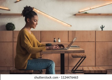 Side view of beautiful Afro American girl in casual clothes smiling while working with a laptop in cafe