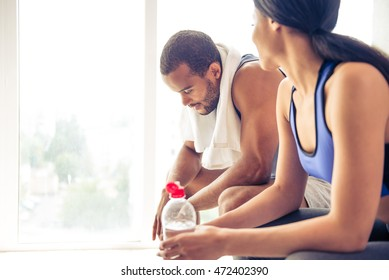 Side view of beautiful Afro American couple in sports clothes drinking water, talking and smiling while resting after workout
