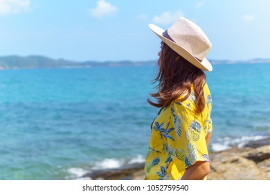 side view of beautiful asian female in fashion yellow shirt stand on the beach looking forward to see amazing blue sky with a little cloud and seascape in a sunny day