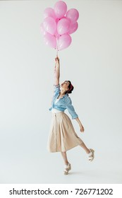 side view of beautiful asian woman in retro style clothing holding balloons isolated on grey