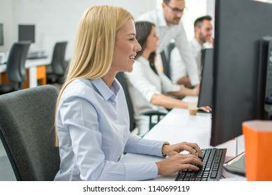 Side view of beautiful blonde hair business woman working on computer in office