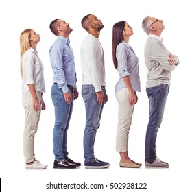 Side view of beautiful business people in smart casual wear looking upward and smiling while standing one by one on a white background