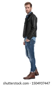 side view of a beautiful casual man with black leather jacket standing with one hand in his pocket serious on white studio background
