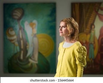 side view of beautiful caucasian woman contemplating artworks in an art museum