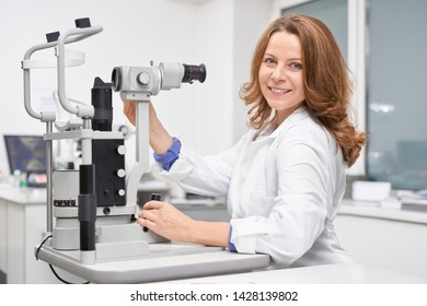 Side view of beautiful female eye doctor working in clinic and checking eyesight with slit lamp. Skilled oculist sitting at table, looking at camera and posing. Concept of ophthalmology.