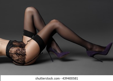 side view of beautiful female legs in stockings and heels over gray background