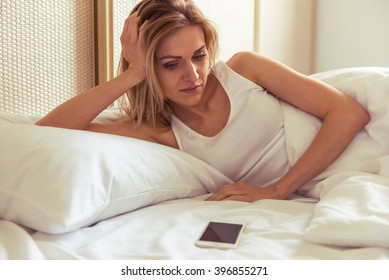 Side view of beautiful girl looking at a mobile phone while lying in bed