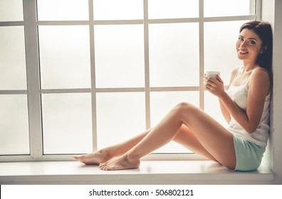 Side view of beautiful girl in pajama holding a cup of coffee, looking at camera and smiling while sitting on the window-sill at home