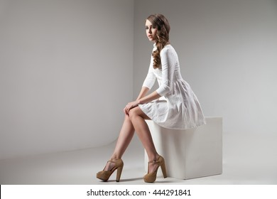 Side view of beautiful girl sitting in white dress