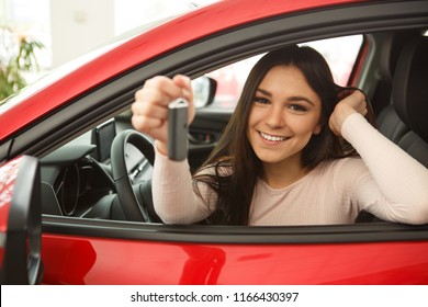 Side view of beautiful girl smiling and looking at camera. Gorgeous young woman holding keys of her new red auto. Happy female client of car dealership buying automobile.
