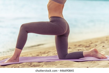 Side view of beautiful girl in sport clothes doing yoga on mat on the beach, cropped