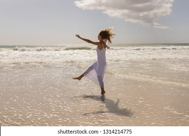 Side view of beautiful happy young woman kicking water on beach in the sunshine