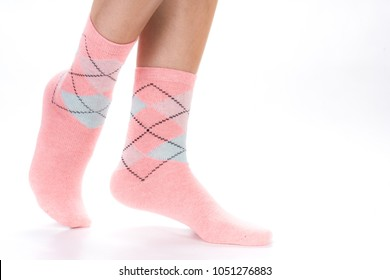 Side view of beautiful human foot dressed in new nice and soft natural cotton fabric blank sock isolated on abstract white background. Wearing and sport clothes concept. Detailed closeup studio shot.