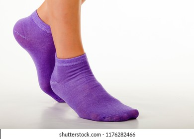 Side view of beautiful human foot dressed in new nice and soft natural cotton fabric blank sock isolated on abstract white background. Wearing and sport clothes concept. Detailed closeup studio shot