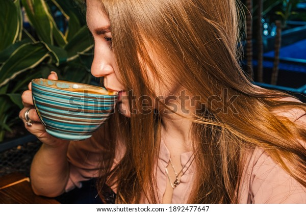 Side view of beautiful lady lond blond hair drinking from cup of coffee in hands. Cropped Image Of lass Having Coffee Drink