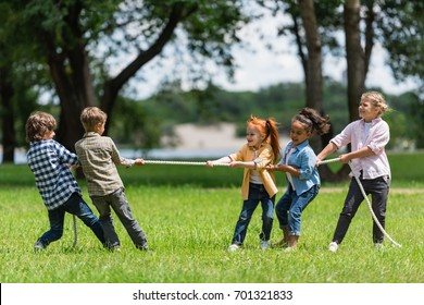 side view of beautiful little multiethnic kids playing tug of war in park