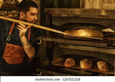 Side view of beautiful man with beard in apron getting out bread using special tool. Professional baker standing near convection oven and looking at fresh baked bread.