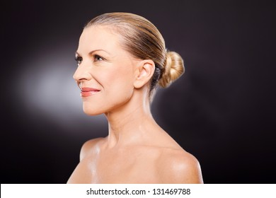 side view of a beautiful middle aged woman on black background