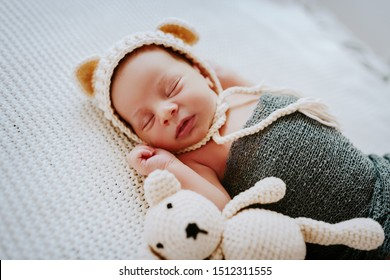 Side view of beautiful newborn baby wrapped in wool scarf and with cap on head sleeping next to toy.