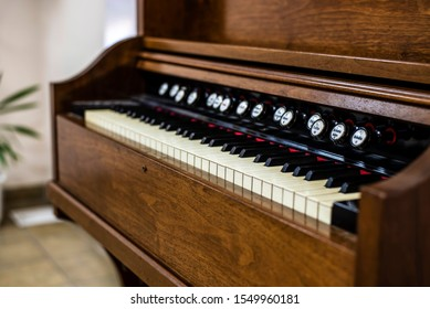 Side view of a beautiful old piano. Piano ancient but in working order, it can be successfully played, selective focus on the keys, close up