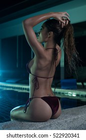 Side view of beautiful sensual woman in sexy velvet maroon bikini with wet hair sitting on the edge of swimming pool during summer evening over amazing green lights background