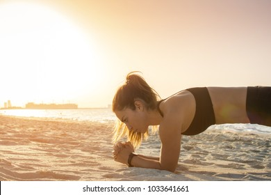 Side view of beautiful sporty woman in plank position on the beach during sunset.