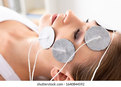 Side view of beautiful woman with electrodes on face during electrode treatment in clinic