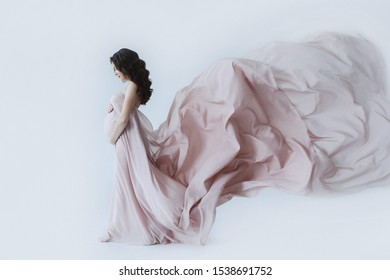 Side view of beautiful woman with long curly brunette hair, wearing in long pink pale dress touching stomach and looking down. Pregnant happy girl, expecting and anticipation to baby.