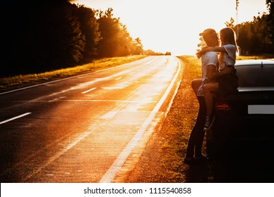 Side view of beautiful woman sitting on car trunk passionately embracing man holding hands around her waist on backlit background of empty road and trees in evening