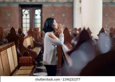 Side view of a beautiful woman sitting in the church while praying to GOD