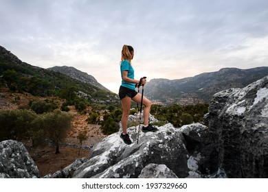 side view of beautiful woman tourist with trekking poles standing on large stone against sky and mountains in Turkey