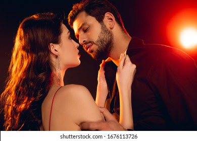 Side view of beautiful woman unbuttoning shirt of boyfriend on black background with lighting