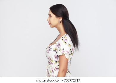 Side view of beautiful young adult woman, standing alone at gray background. Studio shot