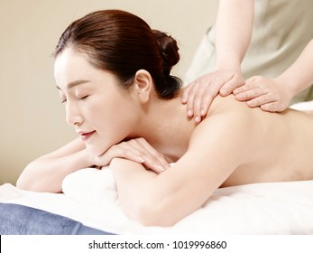 side view of a beautiful young asian woman receiving massage in spa salon, eyes closed.